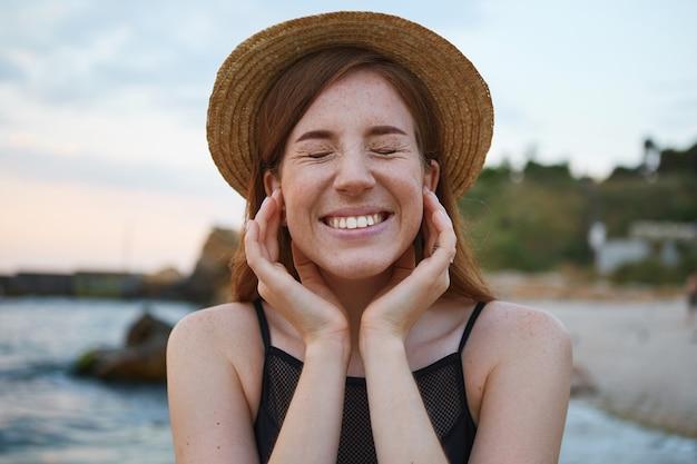 Primo piano di giovane donna lentiggini carino zenzero cammina sulla spiaggia, indossa un cappello, tocca le guance, in generale sorride con gli occhi chiusi, sembra positivo e felice.