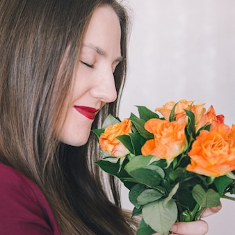 Close-up of a young girl holding a bouquet of orange roses in front of her and sniffing it