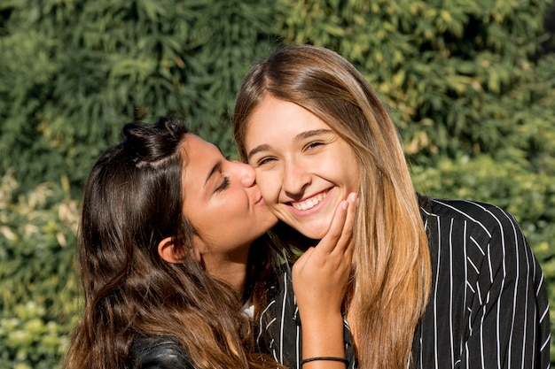 Close-up of young girl kissing her smiling female friend in park