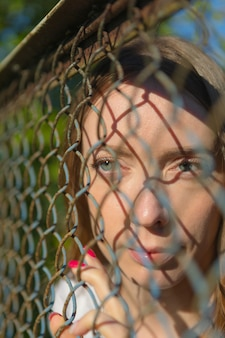 Close-up. a young girl in a park looks through a metal fence.