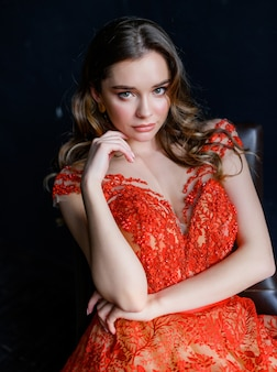 Close up of young girl in a red dress sits on a chair and looks at the camera