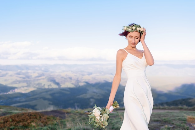 Close up of young girl in a white dress with a wreath on his head and a bouquet of flowers outdoors