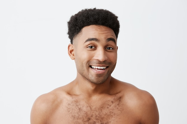 Close up of young good-looking attractive cheerful black-skinned man with afro hairstyle with naked torso smiling with teeth, looking in camera with happy an relaxed expression. health and beauty