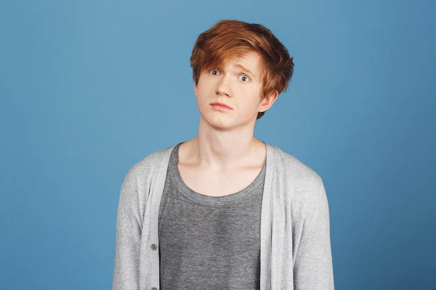 Close up of young good-looking happy red-haired guy in gray t-shirt under cardigan  with confused expression, after receiving hard question on exam in university.