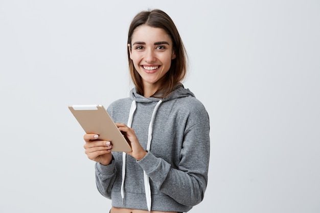 Close up of young good-looking joyful caucasian girl with dark long hair in gray sporty hoodie smiling with teeth, playing games on digital tablet,