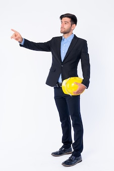 Close up of young handsome bearded persian businessman in suit holding hardhat isolated