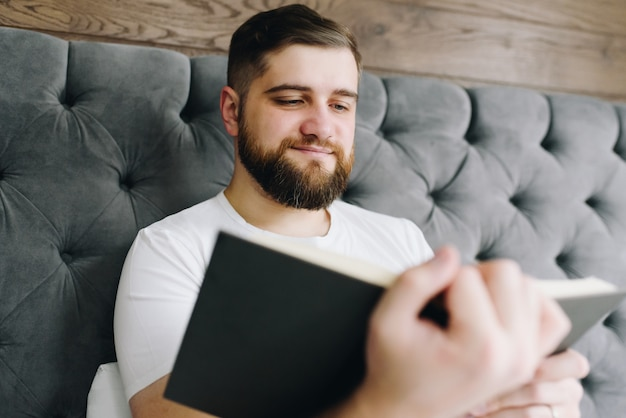 Close up young handsome caucasian man reading a book in bed and smiling