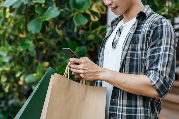クローズアップ、紙袋を持っている若いハンサムな男