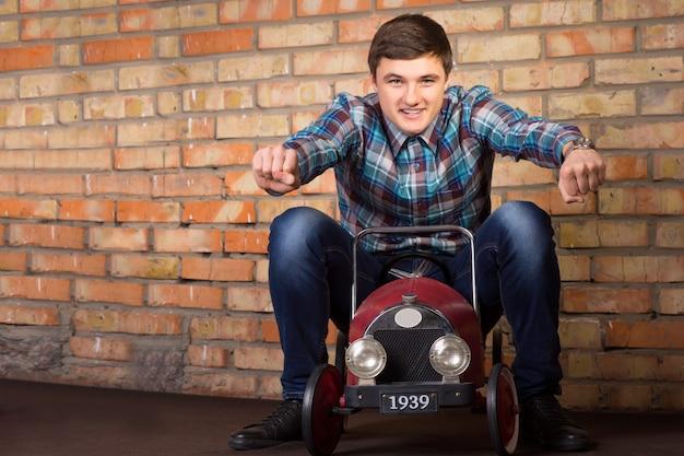 レンガの壁の背景にヴィンテージのおもちゃの車に乗ってカジュアルな服装で若いハンサムな男を閉じます。レーシングコンセプトを強調。