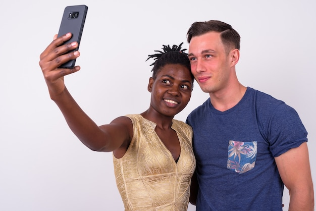 Close up of young handsome man and young african woman together and in love isolated