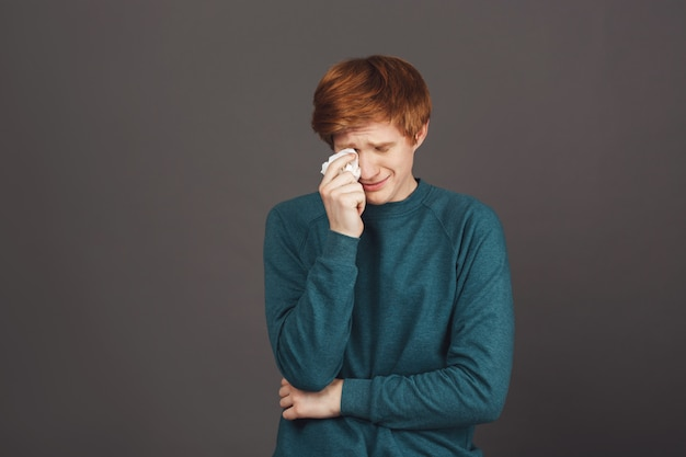 Close up of young handsome sensitive ginger teenager in green sweater crying, wipes tears with paper napkin, being tired of bad relationships with parents, that don't allow him go to the party.