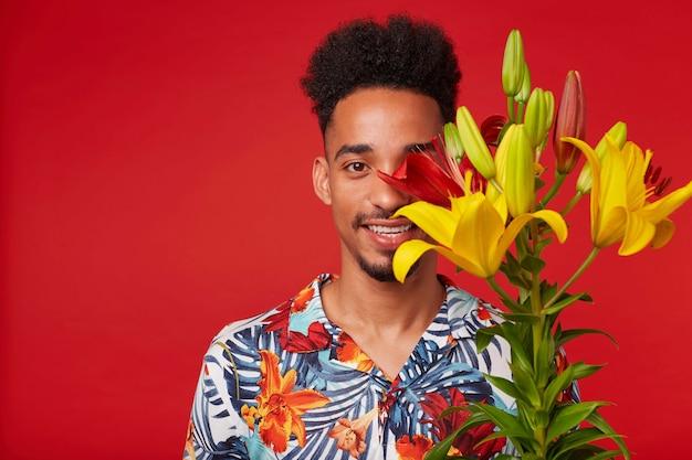 Primo piano di giovane uomo afroamericano felice, indossa in camicia hawaiana, guarda la telecamera con espressione felice, detiene fiori gialli e rossi e il viso coperto, si erge su sfondo rosso.