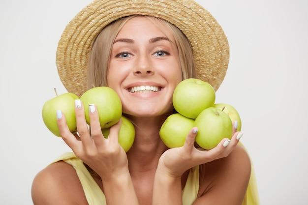 Primo piano di giovane donna bionda attraente felice con trucco naturale mantenendo le mele verdi vicino al suo viso mentre guarda con gioia la fotocamera con un ampio sorriso, isolato su sfondo bianco