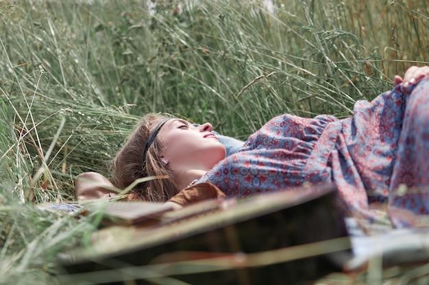 クローズアップ。草の上に横たわって休んでいる若いヒッピーの女性
