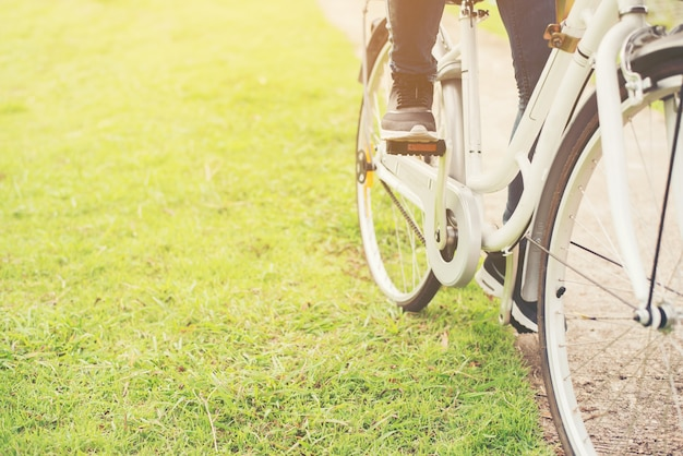 Close-up of young hipster woman holding her foot on bicycle peda