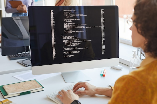 Close up of young it developer writing code on computer screen while working in software production studio, copy space