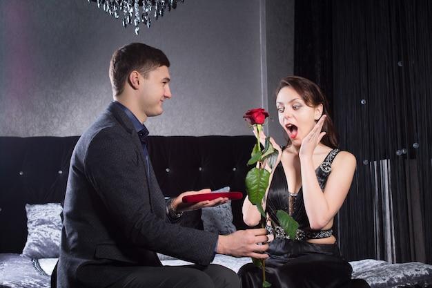 黒のドレスを着た若い女性をクローズアップサプライズリアクションで彼女のボーイフレンドからジュエリーと赤いバラのプレゼントを受け取りました。寝室で捕らえられた。