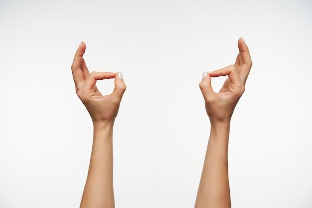 Chiuda in sulle mani della giovane signora con il manicure bianco che forma il gesto di murda
