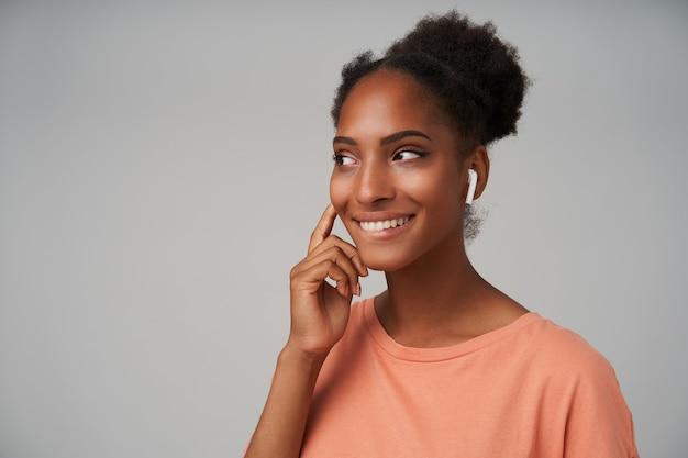 Primo piano di giovane bella donna bruna dalla pelle scura mantenendo la mano alzata sul suo auricolare e sorridendo felicemente mentre guarda da parte, in piedi sul grigio