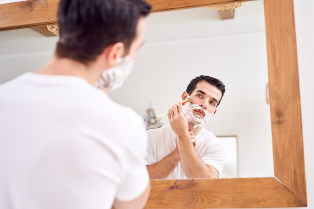 Крупным планом молодой мужчина в белой футболке бреется, стоя возле зеркала в ванне утром