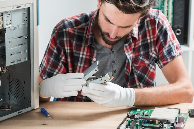 Close-up of a young male technician examining computer part