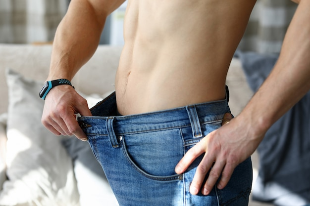 Close-up of young male wearing oversized pants. person showing big difference in size. slim and athletic man in jeans. body care. weight loss and strong diet concept