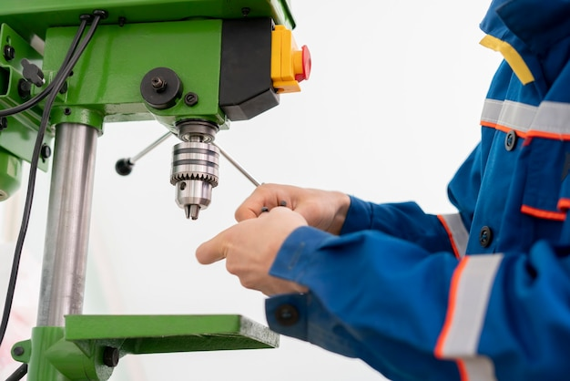 A close up young male worker using a drill machine on the factory