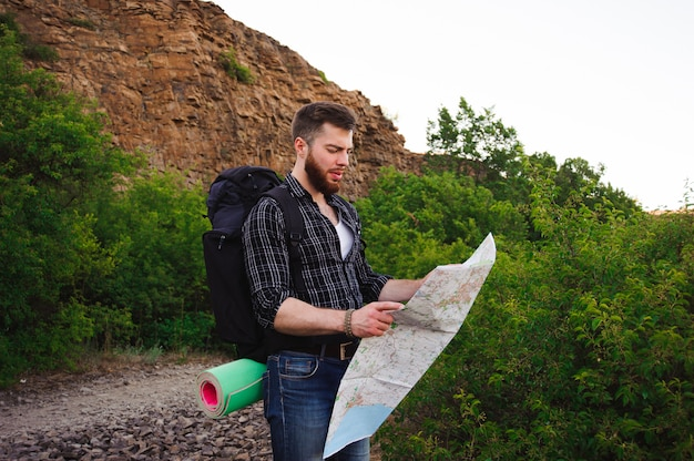Close up of a young man as he reads the map, traveling alone - lifestyle, people, outdoor and holiday concept.