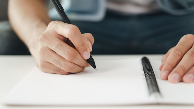 Close up of young man in casual cloth hands writing down on the notepad, notebook using ballpoint pen on the table.