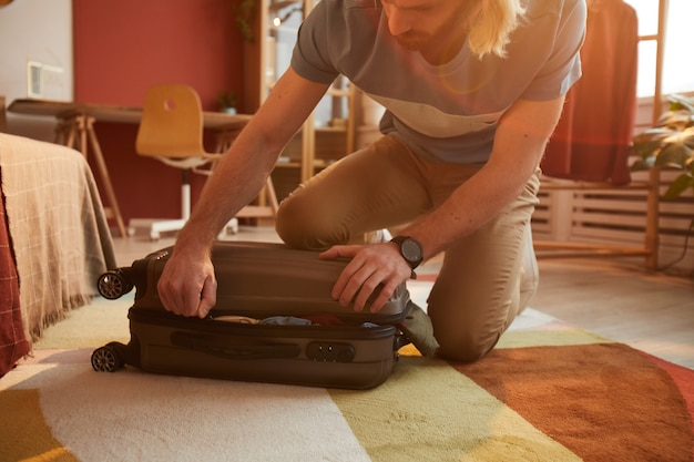 Close-up of young man closing his suitcase full of clothes and preparing for his journey