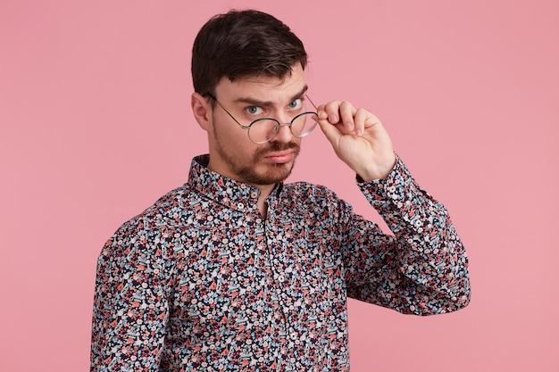 Primo piano di giovane uomo in camicia colorata, con espressione del viso confuso mentre, guardando attraverso gli occhiali avendo dubbi, isolato su sfondo rosa.