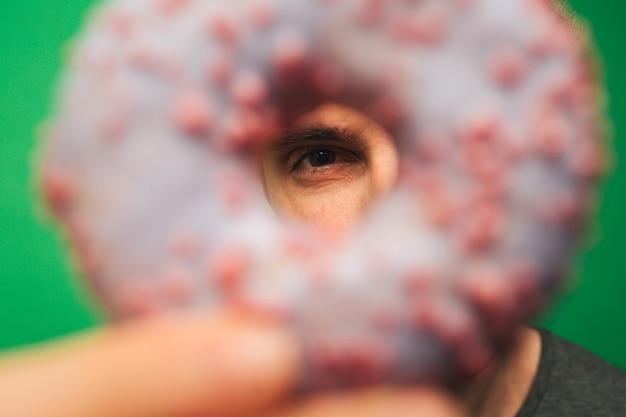 クローズアップ若い男は、緑の背景に分離されたドーナツで目を覆います。