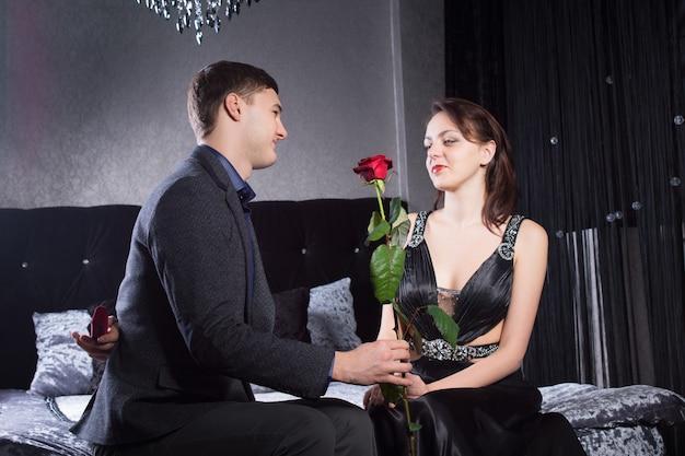 彼の幸せなガールフレンドに赤いバラの花を与える若い男を閉じます。両方がベッドに座っている間に寝室で捕らえられた。