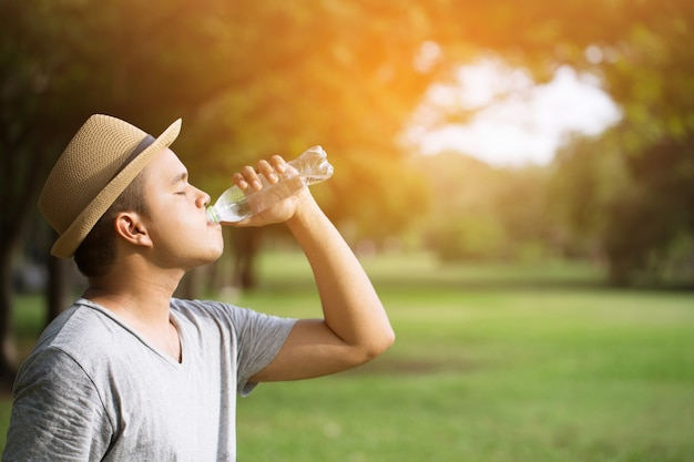 プラスチック製の冷たい新鮮な飲料水のボトルを持っている若い男の手を閉じます。