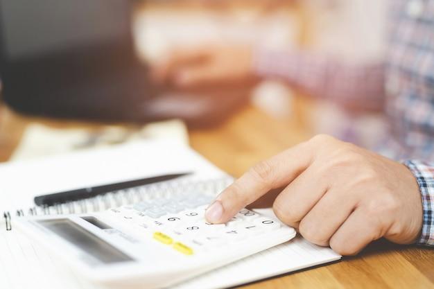 クローズアップの若い男の手は、ノートに書き込み、電卓を使用してメモを作成します。ホームオフィスで財務を行う際の会計。貯蓄財政の概念。