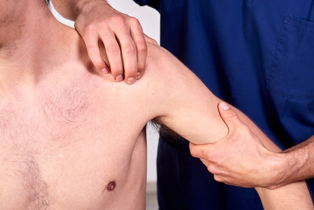 Close-up of a young man having chiropractic shoulder adjustment.