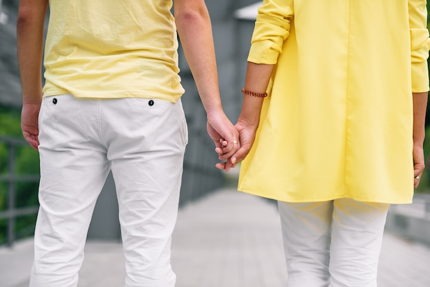 Close up young man and his girlfriend in casual clothes holds the hands to each other. view from back.