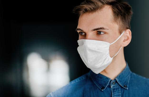Закройте вверх. молодой человек в защитной маске. концепция охраны здоровья.