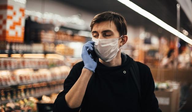 Закройте вверх. молодой человек в защитной маске разговаривает по своему смартфону. гигиена и забота о здоровье