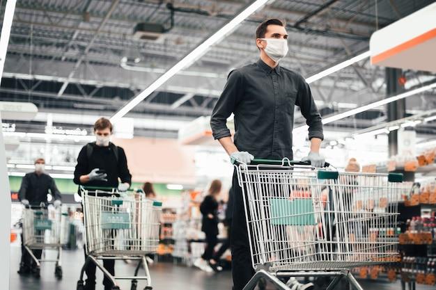 Закройте вверх. молодой человек в защитной маске с тележкой для покупок