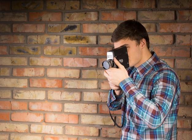 벽돌 벽 배경에 휴대용 장치를 사용하여 무언가를 녹음하는 체크 무늬 긴 소매 셔츠에 젊은 남자를 닫습니다.