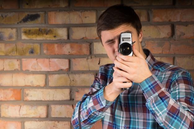 벽돌 벽 배경에 휴대용 카메라를 사용하여 뭔가를 캡처하는 체크 무늬 셔츠에 젊은 남자를 닫습니다.