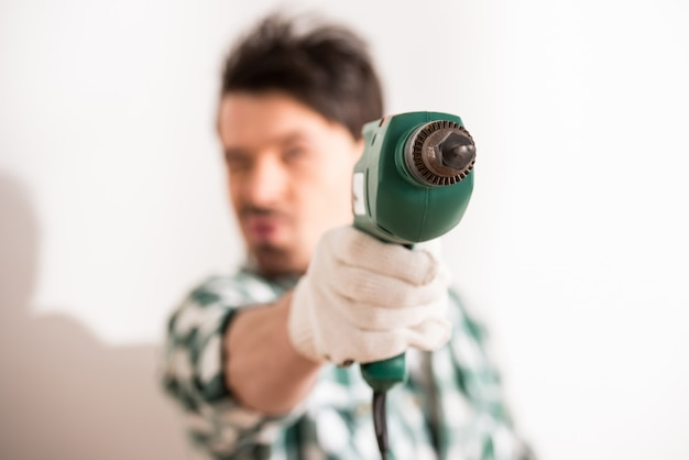 Close-up of young man is holding electric drill.