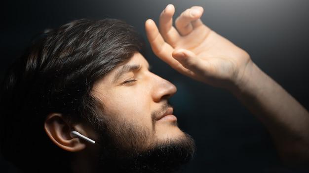 クローズアップの若い男、黒い壁にワイヤレスイヤホンで音楽を聴きます。