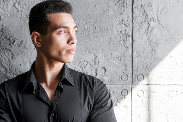 Close-up of a young man looking away standing against grey wall