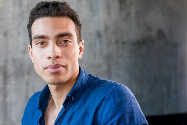Close-up of a young man looking at camera against grey wall