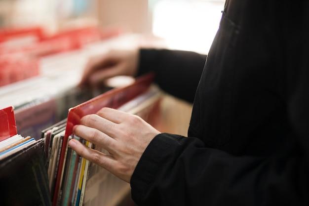 Крупным планом молодой человек ищет винилы в магазине