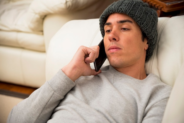 Close-up of young man lying on sofa talking on smartphone