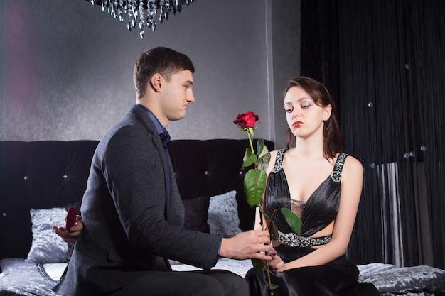 彼の背中の後ろに宝石箱を持っている間、悲しいガールフレンドにバラの花を提供している若い男を閉じます。寝室で捕らえられた。