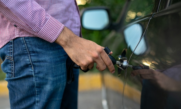 Close up of a young man opening a car door he opens the car door with his key